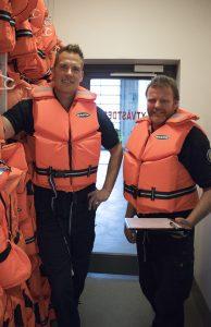 Två manliga brandmän klädda i flytväst.