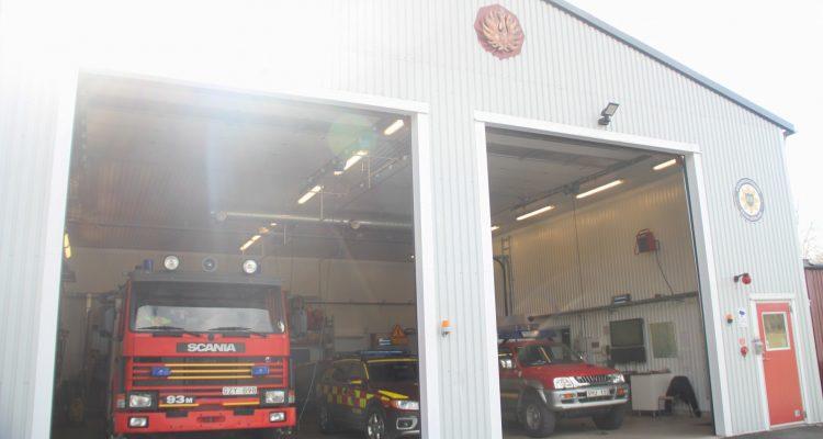 En vit brandstation med öppna portar, där man ser in på tre räddningsfordon. Stationen ligger i Bestorp.