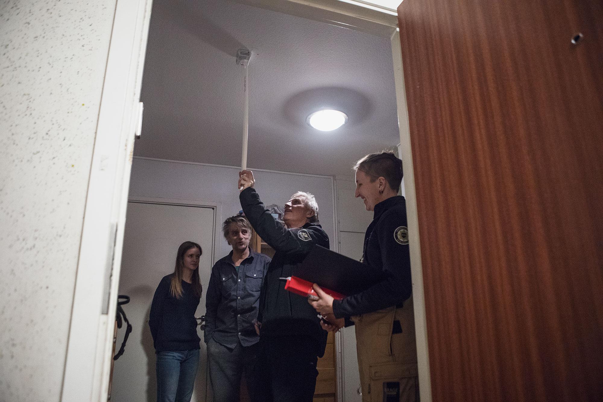 Bild på två brandmän som testar om brandvarnaren fungerar i en lägenhet