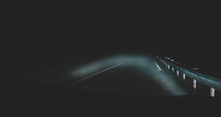 Bild på mycket mörk väg. Man anar vägräcken på sidan. Bilden illustrerar hur dåligt man syns i mörker utan reflexer.