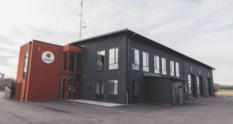 En mörkgrå brandstation med röda detaljer. Räddningstjänstens emblem pryder fasaden.