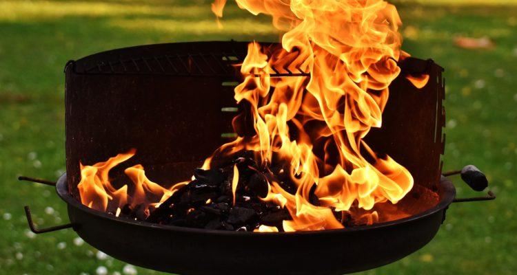 Närbild på en grill med kraftigt flammande lågor.