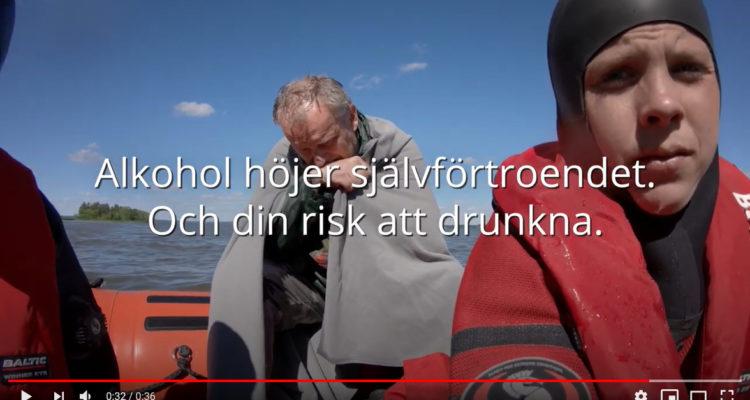 """Utsnitt ur en film. Man ser en vattendykare (en brandman) som håller tag i vad som upplevs vara en själv. Hon drar """"dig"""" upp ur vattnet och upp i en båt. I bakgrunden ser man en man i övre medelåldern, frusen blöt och med en filt omkring sig."""