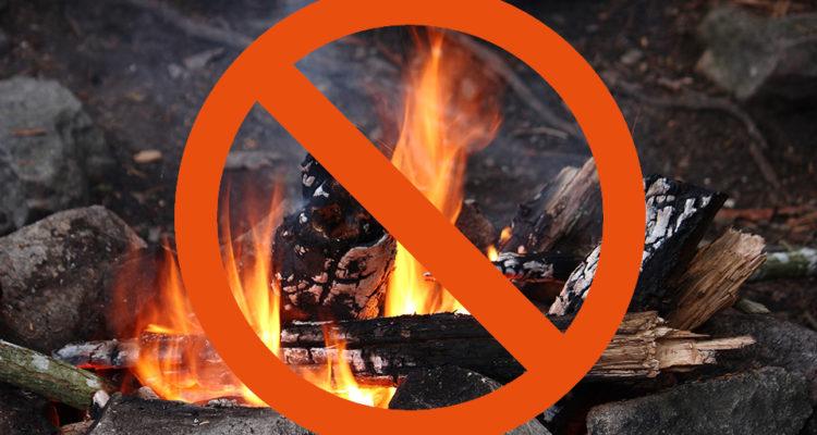 En brasa med en stor röd förbudsskykt ovanpå, som signalerar förbud mot att elda.