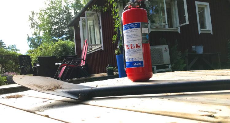 En brandsläckare står intill en liggande spade, framför ett hus i somrig miljö.