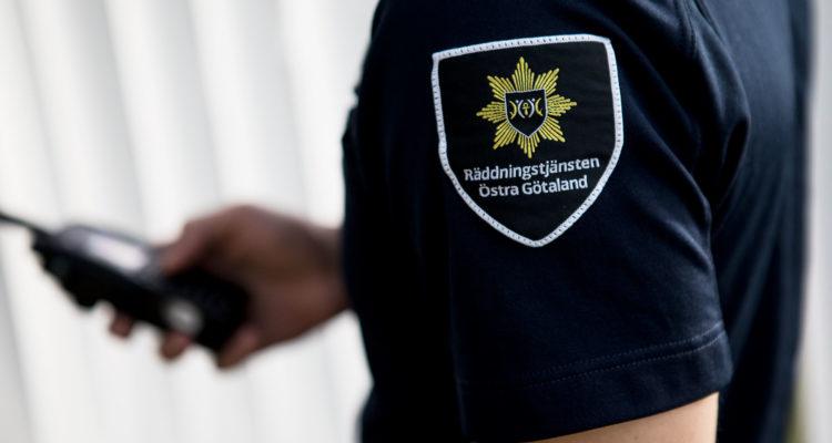 Man ser sidan av en person, men inte ansiktet eller underkroppen. Personen har en kortärmad blå uniformströja med Räddningstjänsten Östra Götalands emblem på axeln. I bakgrunden ser man att hen håller i en telefon.