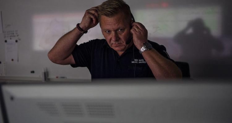 En medelålders man med headset sitter vänd mot kameran framför en dator. Han är inre befäl på vår räddningscentral.