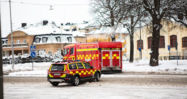 Två utryckningsfordon, en befälsbil och en släckbil, lämnar station Centrum i Norrköping. det är snö på marken. I bakgrunden ser man rondellen Södra promenaden/Kungsgatan.