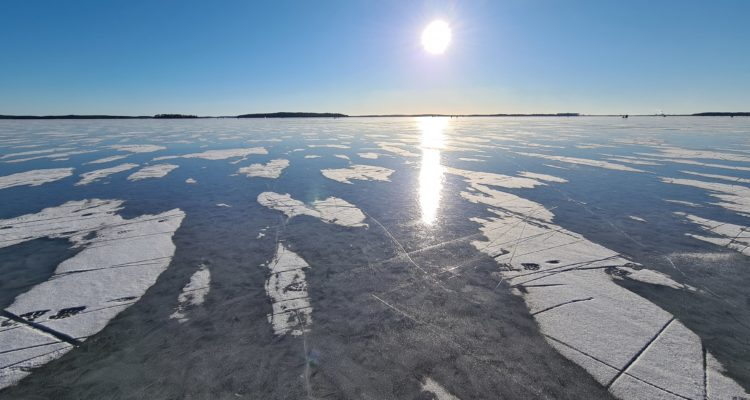 Vy över en frusen havsvik. Solen skiner över den blanka isen.