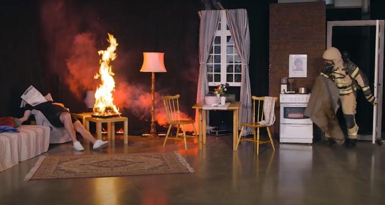En scen där en man ligger på en säng till vänster i bild. han har en tidning liggande över sig och man förstår att han sover. Bredvid honom brinner det på en stol, och från dörren till höger i bild kommer en brandman i utryckningskläder, redo att släcka branden.