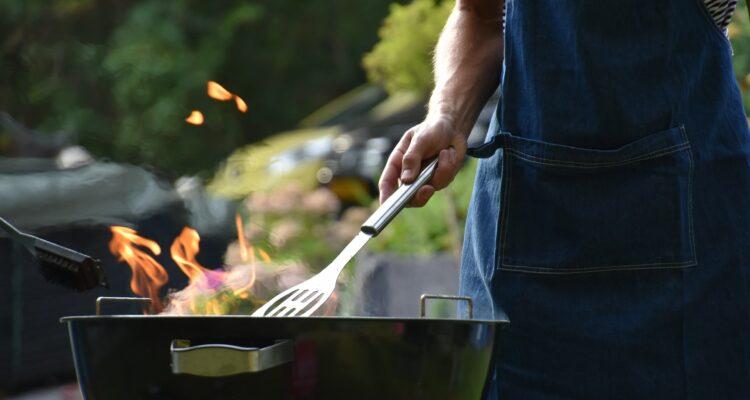 Inzoomad bild på en brinnande grill, med en hand som håller i en grillspade.