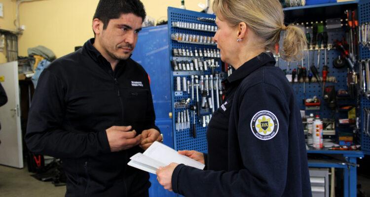 En man och en kvinna i mörkblåa rädddningstjänstkläder samtalar framför ett skåp med verktyg.